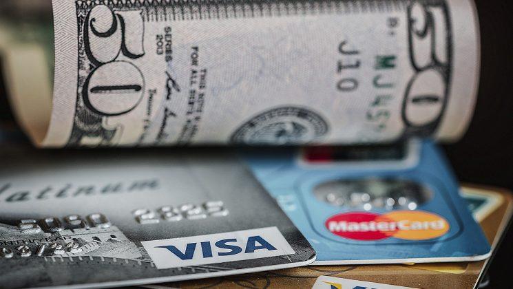 Sechs Dinge, für die eine Kreditkarte unabdingbar ist. Mehrere Kreditkarten und ein Geldschein auf einem Tisch